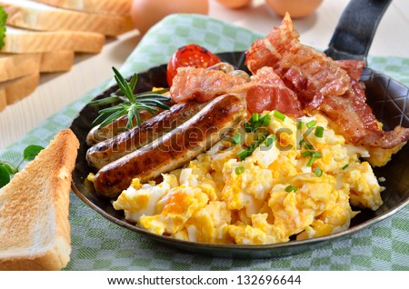 Scrambled eggs with fried bacon, fried sausages, grilled tomato and toast