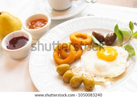 Scrambled eggs with olives, anchovies,potato rings, green leaves on the plate, coffee Cup, and pear jam. #1050083240