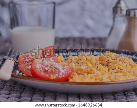 Scrambled eggs with tomatoes and cheese,shot close up,there is some milk and some condiments in the background.