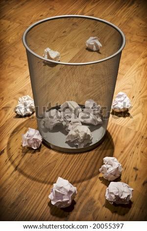 Scrap paper on wooden floor around waste paper basket - stock photo