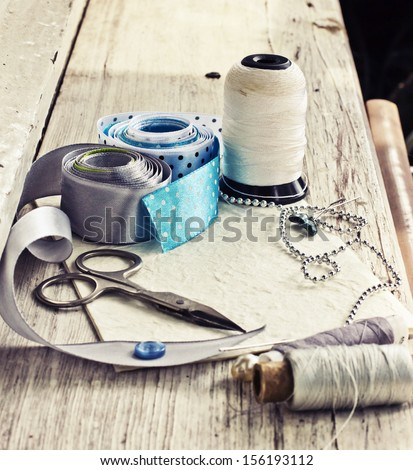 Scrapbooking Craft Materials/ Background With Sewing Tools And Colored Tape/Sewing Kit. Scissors, Bobbins With Thread And Needles On The Old Wooden Background
