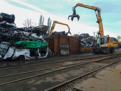 Scrapped crushed cars and hydraulic Claw Crane in recycling site