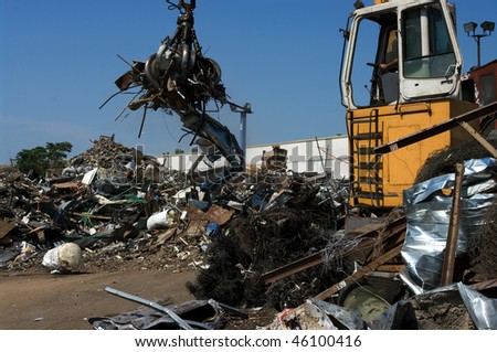 Scrapyard with a grabber - stock photo
