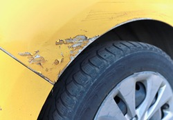 Scratched front right fender of a yellow car. Damaged car wing. Car accident. Auto insurance.