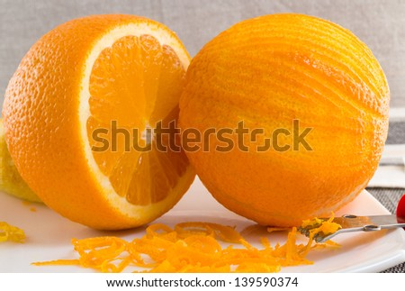 Scratched orange on white plate and thin curls of orange peel