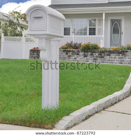 Scratched Suburban Gray Mailbox on front yard lawn in residential neighborhood on cloudy overcast day