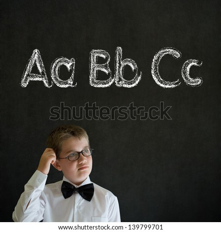 Scratching head thinking boy dressed up as business man with learn English language alphabet on blackboard background