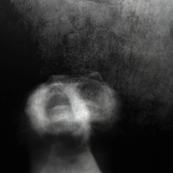 Scream of horror. Screaming woman face. Surreal portrait of a mysterious young woman. Black and white photo. Shot with long exposure.