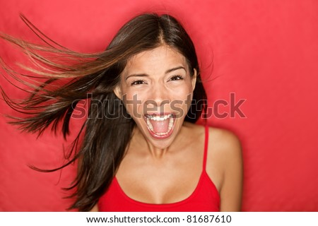 Scream. Woman screaming wild and crazy at full energy looking at camera on red background. Beautiful mixed race Asian Caucasian brunette female model with wind in the hair.