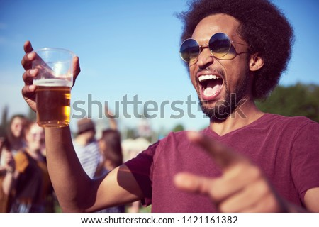 Screaming African man drinking beer at the music festival  #1421161382