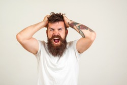 Screaming and angry man. Screaming bearded brutal man over white background. Face expression. Crazy man with beard. Negative emotions, problems. Stressed guy shouting.