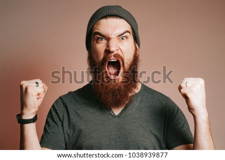 Screaming bearded brutal man and looking at the camera with hands up, Goal, Winner, Celebrating. Face expression. Crazy man with beard.