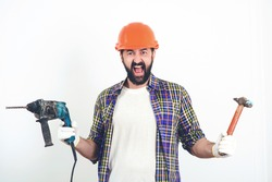 Screaming builder in helmet. Bearded man holding drill and hammer. Butal builder man. Construction worker in hard hat. Builder working with construction helmet. Builder with professional tools.