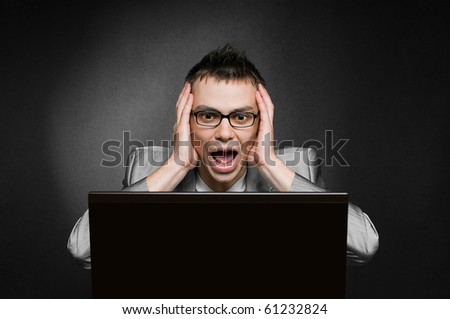 screaming businessman with laptop on black background