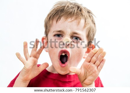screaming cheeky kid with a missing tooth crushing his nose and hands to a window for the concept of misbehavior and child violence, white background