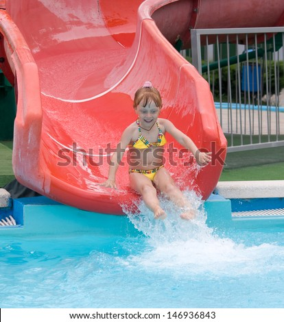 Screaming girl riding down the water slide