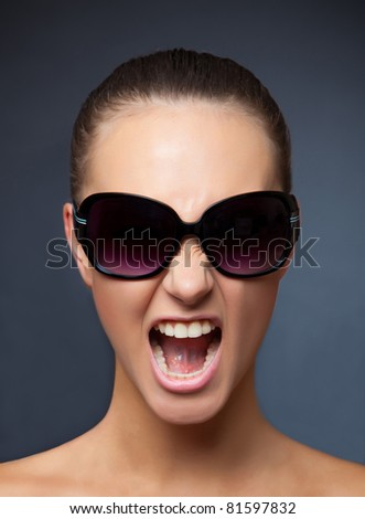 Screaming girl with sunglasses, vertical studio isolated shot