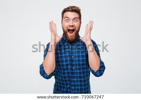 Screaming happy bearded man in casual looking camera and screaming isolated over white #710067247