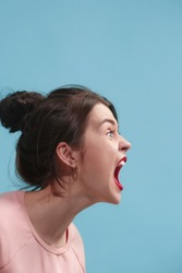 Screaming, hate, rage. Crying emotional angry woman screaming on blue studio background. Emotional, young face. Female half-length portrait. Human emotions, facial expression concept. Trendy colors