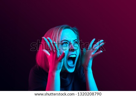 Screaming, hate, rage. Crying emotional angry woman screaming on neon studio background. Emotional, young face. Female half-length portrait. Human emotions, facial expression concept. Trendy colors