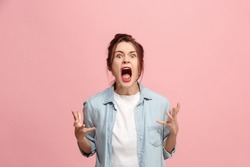 Screaming, hate, rage. Crying emotional angry woman screaming on pink studio background. Emotional, young face. Female half-length portrait. Human emotions, facial expression concept. Trendy colors