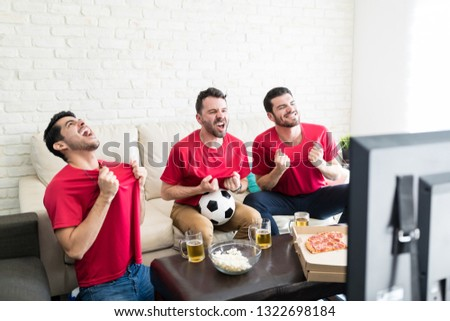 Screaming Latin fans pulling jerseys after their favorite team scores winning goal  #1322698184