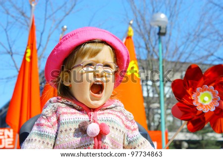 Screaming little girl 2 years old wearing glasses in pink hat and red flags