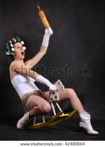 Screaming militant feminist with rolling pin ridden on a wooden hobby horse. Humorous image. Great for calendar. - stock photo