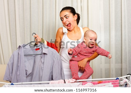 Screaming young mother fed up with doing the laundry, holding her crying child and talking on the phone in the same time.