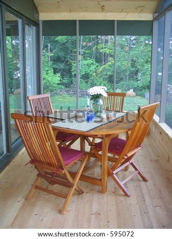 Screened in cottage porch with teak table and chairs set and ready for entertaining