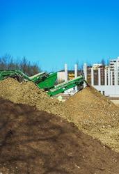 Screener machine working. Heavy equipment on construction site.