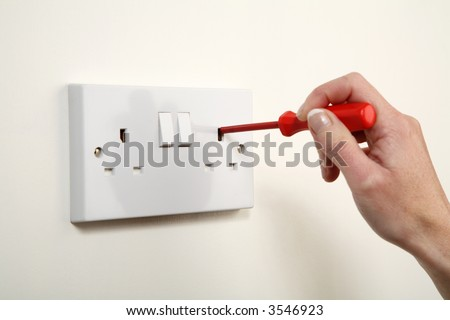 Screwdriver being pushed into a UK wall socket