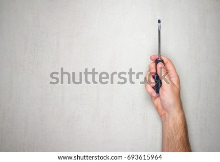 screwdriver in male hand on gray background, top view. mock up for text, phrases, lettering