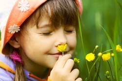 screwed-up girl closeup smelling a yellow flower on a green background