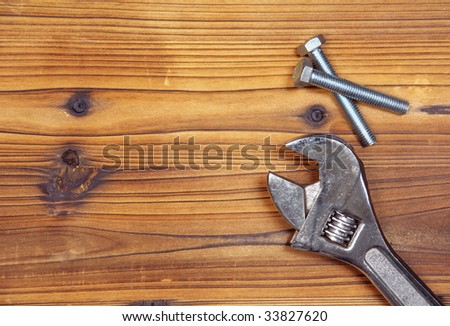Screws and spanner on wood board. Background pic with screws and spanner at the right. Space for your text on the left.
