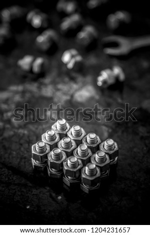 screws, bolts and nuts with spanner on wooden texture, screws, bolts, nuts and spanner with black background, linear arrangement of screws, nuts and bolts