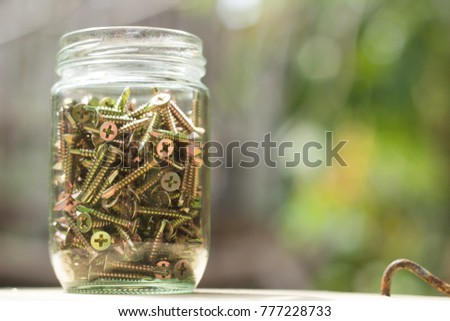 Screws in glass Jar with park outdoor background. Engineer and construction tool, Mechanical Grease Concept