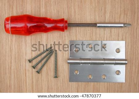 Screws, screwdriver and steel hinge. #47870377