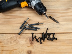 screws screws and dowels nails on the background of a screwdriver, a selection of different screws screws and dowels for different materials of walls and surfaces