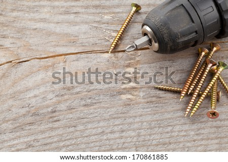 Screws with power drill on old wooden plank