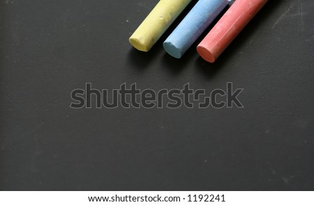 Scribble down the facts : Four multi colored chalks on black board
