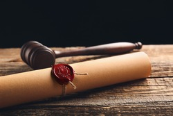 Scroll with notary public wax seal and gavel on table