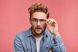 Scrupulous stylish man in denim shirt and spectacles looks with shocked and stupefied expression, tries understand what is written. Strict professor listens to student`s answer, being in stupor