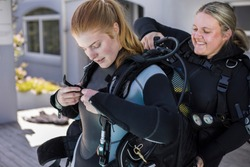 Scuba dive buddies helping each other to put on their BCDs.