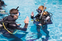 Scuba dive training in a pool students showing the ok sign above water.