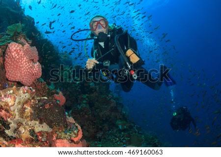 Scuba dive. Woman scuba diver. Scuba diving coral reef with fish #469160063