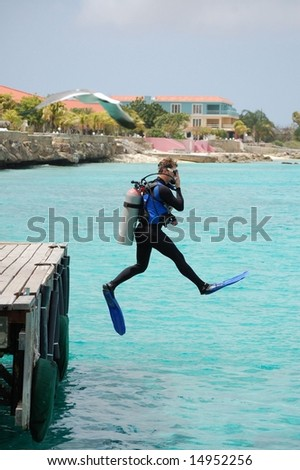 "Scuba diver doing perfect ""giant stride"" off dock."