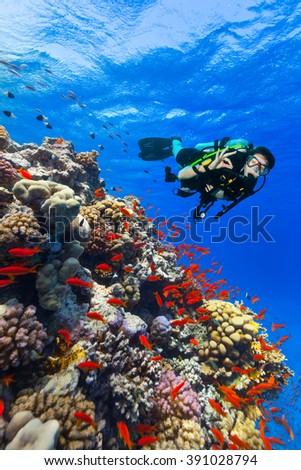 Scuba diver explore a coral reef showing ok sign