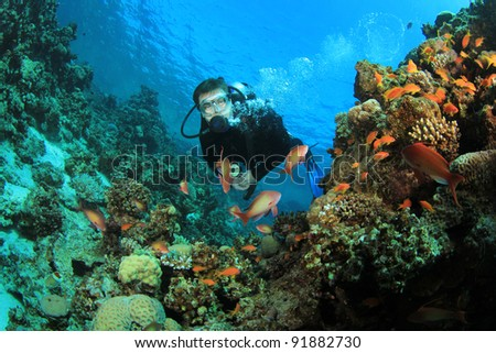 Scuba Diver explores Coral Reef #91882730