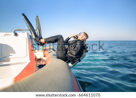 Scuba diver jumping in the water from a boat #664611070